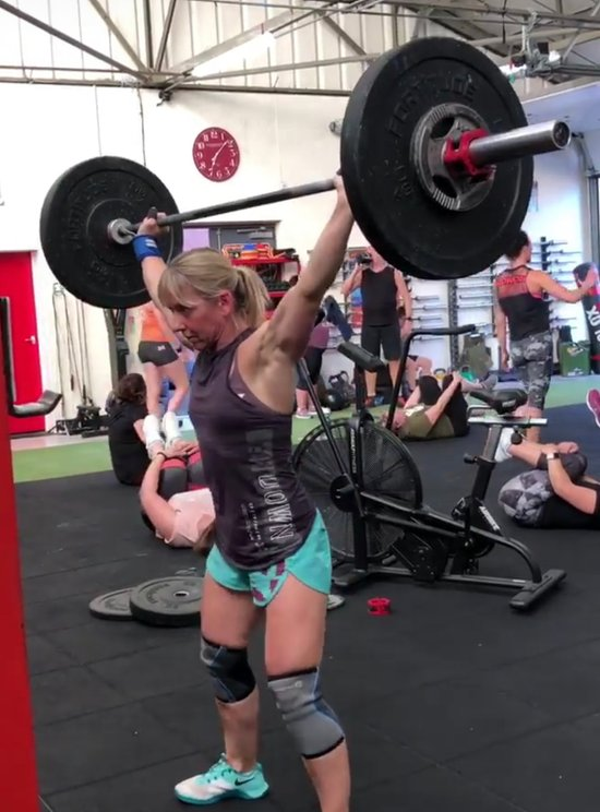 athlete doing overhead squats in gym