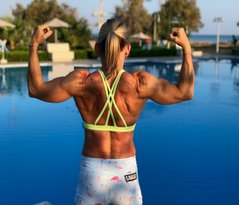 athlete doing double bicep pose showing back muscles by pool