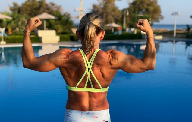 dawn french twd fitness personal trainer double bicep pose in front of pool showing back muscles during her fitness routine