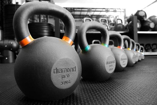 kettlebells lined up on floor of daventry personal trainer gym